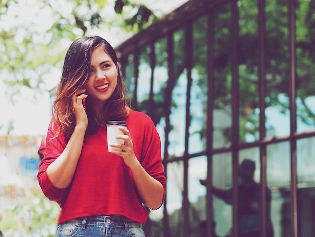 Femme asiatique parlant au téléphone pendant que vous buvez du café à l'extérieur.