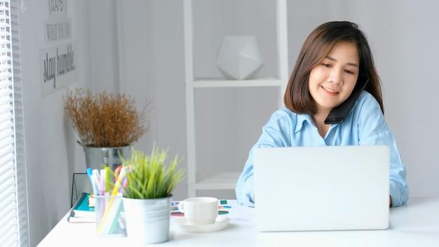 Femme asiatique parlant de téléphone tout en travaillant avec un ordinateur portable au bureau à domicile