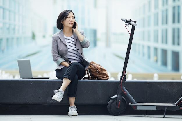 Femme asiatique, parler téléphone, dans ville
