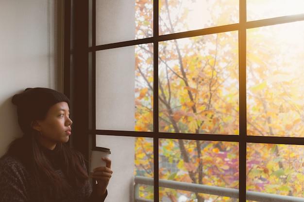 Femme asiatique, penser, tout, boire café, et, debout, dans chambre