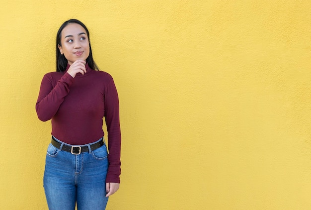 Femme asiatique pensive sur fond jaune