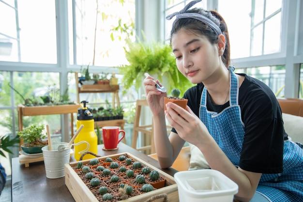 Femme asiatique plantation et jardinier pulvérisation d'eau sur la plante dans le jardin à la maison.