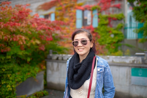 Femme asiatique à pleines dents visage souriant avec fond de parc feuilles colorées