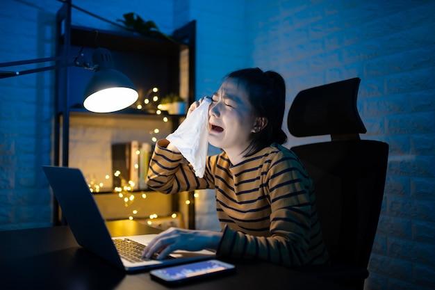 Femme asiatique pleurant et utilisant du papier de soie pour faire des heures supplémentaires à la maison. . travaillez à domicile pour éviter le concept coronavirus covid 19.