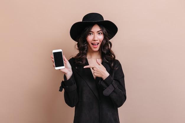 Femme asiatique pointant avec le doigt sur le smartphone avec écran blanc. photo de studio d'une femme coréenne émotionnelle en manteau noir.