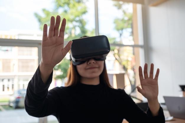 Une femme asiatique portant une caméra vr tout en profitant de jouer à des jeux