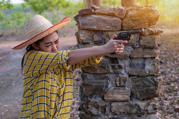 Femme asiatique portant un chapeau à la prise de vue d'un vieux revolver dans le faasia