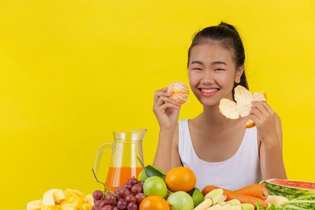 Une femme asiatique portant un débardeur blanc. je suis peeling ou orange et la table regorge de fruits divers.
