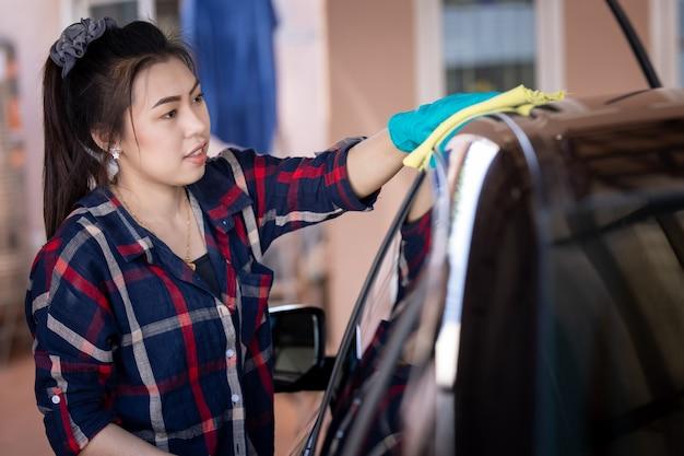 Femme asiatique portant des gants verts nettoyant le toit de la voiture noire avec un chiffon en microfibre jaune