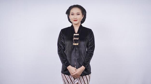 Une femme asiatique portant une kebaya noire a l'air élégante isolée sur fond blanc