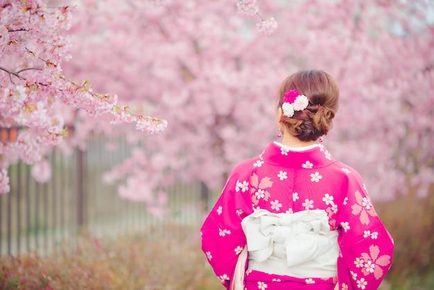 Femme asiatique portant un kimono avec des fleurs de cerisier, sakura au japon.