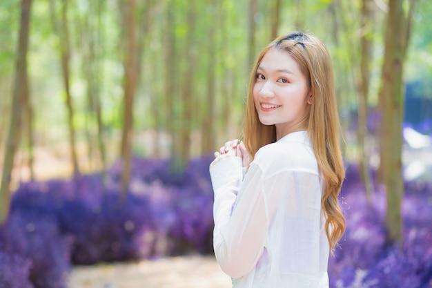 Une femme asiatique portant une longue chemise blanche sourit joyeusement et se tient dans le jardin comme elle est naturelle