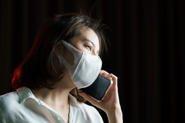 Femme asiatique portant un masque chirurgical faisant un appel téléphonique.