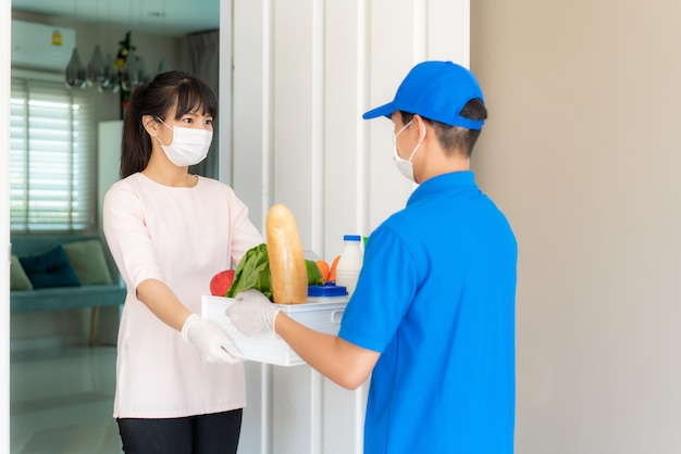 Une femme asiatique portant un masque facial et un gant reçoit une boîte d'épicerie de nourriture, de fruits, de légumes et de boissons d'un livreur devant la maison pendant l'isolement.