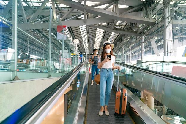 Femme asiatique portant un masque facial et garder la distance avec les autres personnes tout en utilisant l'escalator à l'aéroport