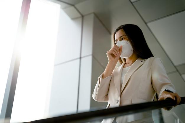 Femme asiatique portant un masque facial n95 pour protéger la pollution pm2.5 et le virus. covid-19 coronavirus et pollution de l'air pm2.5 concept de soins de santé et médical.