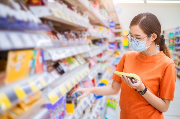 Femme asiatique portant un masque facial pour une marche saine dans les produits de choix du centre commercial sur l'étagère du supermarché.