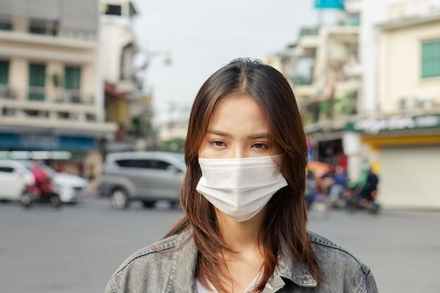 Une femme asiatique portant un masque lorsqu'elle marche dans la rue