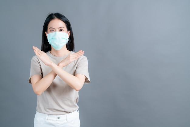 Une femme asiatique portant un masque médical protège la poussière de filtre pm2.5 anti-pollution, anti-smog et covid-19 sur fond gris