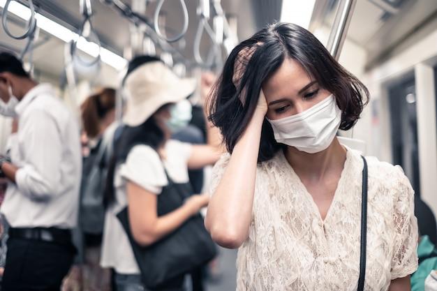 Femme asiatique portant un masque pour éviter le crépuscule pm 2.5 mauvaise pollution de l'air et coronavirus ou covid-19 se propageant en asie ayant des maux de tête dans un train souterrain.