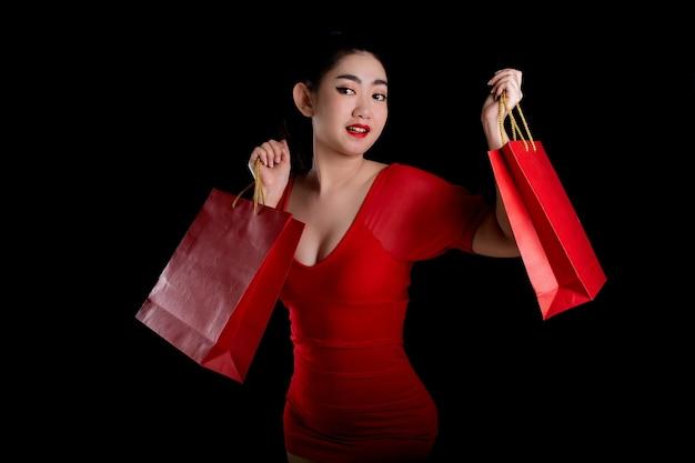 Femme asiatique portant une robe rouge tenant une carte de crédit et des sacs à provisions