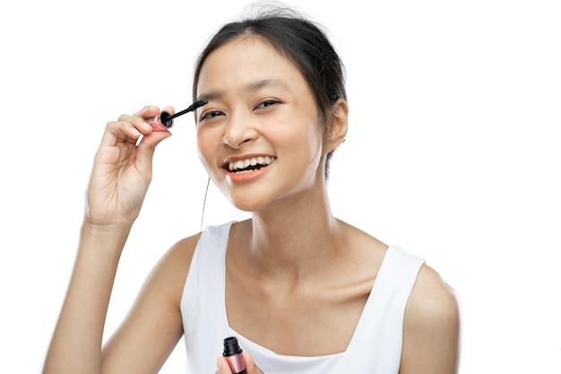 Femme asiatique portant des sous-vêtements blancs utilisant du mascara pour se maquiller