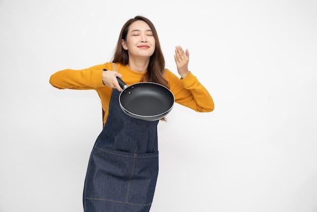 Femme asiatique portant un tablier de cuisine cuisine et tenant la casserole.