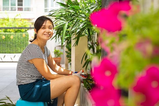 Une femme asiatique porte des gants de jardin et utilise des sécateurs coupés en palmier pour décorer à la maison.verrouillez le temps d'une fille malaisienne dans le jardin.