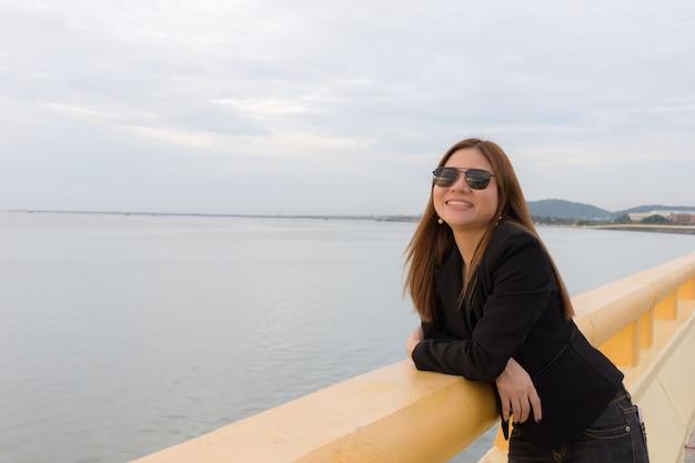 Femme asiatique porte des lunettes de soleil noires debout et souriant sur le pont