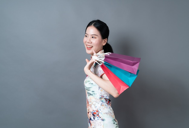 Une femme asiatique porte une robe traditionnelle chinoise avec une main tenant un sac à provisions sur fond gris