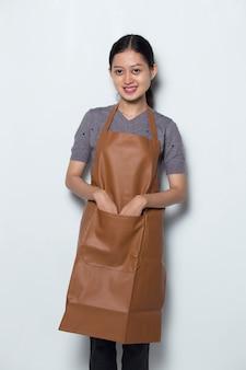 Une femme asiatique porte un tablier de barista croisé ses bras concept de service de café