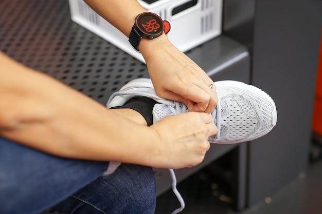Femme asiatique porte et teste la sneaker dans un magasin de chaussures avant de l'acheter