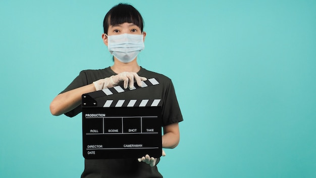 Femme asiatique porter un masque facial main tenir clap noir sur fond vert mentheporter des gants