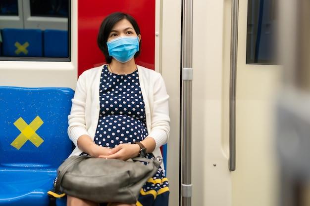 Femme asiatique, porter, masque facial, voyager, travailler, par, métro, dans, ville