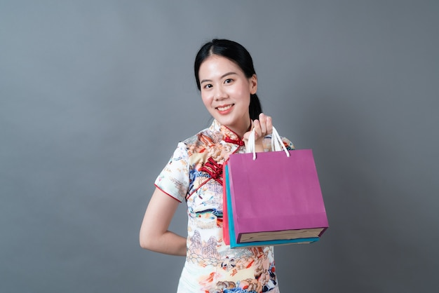 Femme asiatique porter des vêtements traditionnels chinois avec main tenant un sac à provisions sur un mur gris