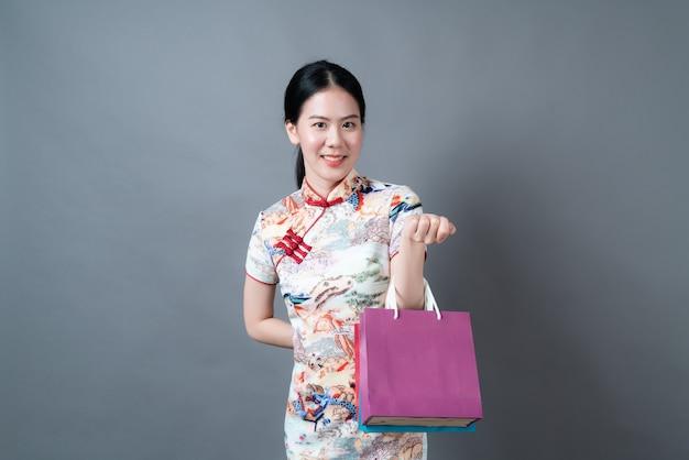 Femme asiatique porter des vêtements traditionnels chinois avec main tenant un sac à provisions sur une surface grise
