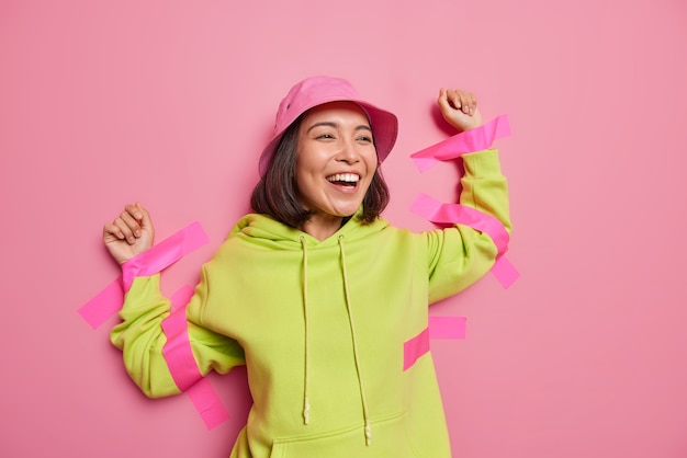 Une femme asiatique positive rit joyeusement collée au mur avec des rubans adhésifs porte un panama et un sweat à capuche ne se sent pas libre isolé sur un mur rose