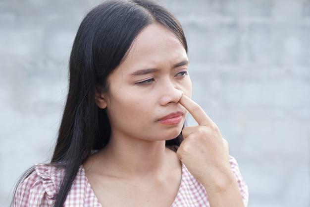 La femme asiatique pousse sa main dans son nez