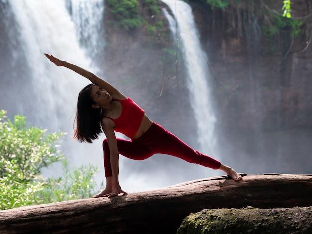 Femme asiatique pratiquant ou faisant du yoga à la cascade