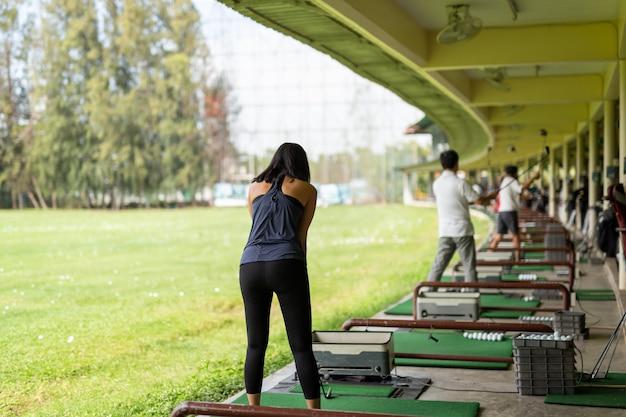 Femme asiatique pratiquant son swing au practice de golf.