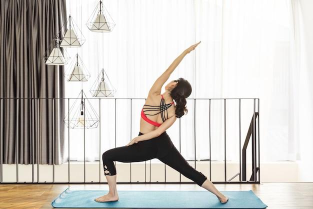 Femme asiatique pratiquant le yoga à la maison lors de l'épidémie de covid19 et du verrouillage en bonne santé ou de la méditation