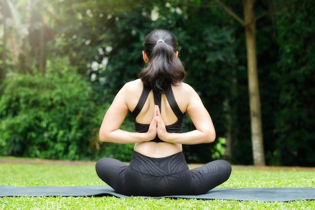 Femme asiatique pratiquant le yoga en posture de prière inversée