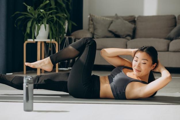 Femme asiatique pratique le yoga à la maison