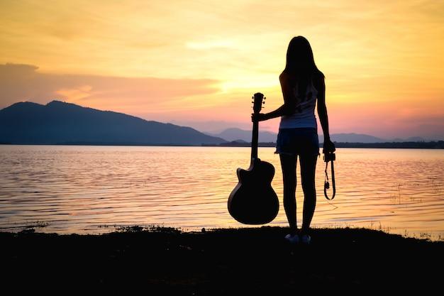 Femme asiatique prenant une photo près du lac en vacances.