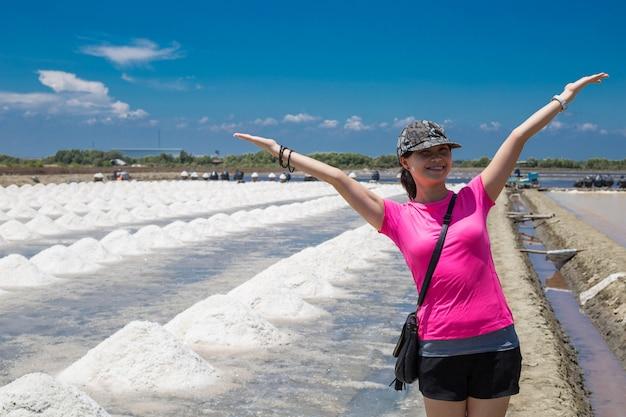 Une femme asiatique prend une photo devant la matière première du sel en thaïlande avec un ciel bleu.