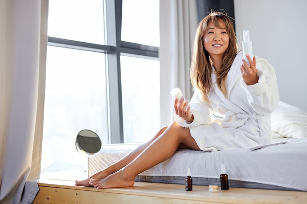 Une femme asiatique prend soin de la peau des jambes, à l'aide de sérum cosmétique, de crèmes pour une peau lisse