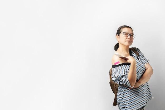 Femme asiatique prête pour un voyage en toute sécurité. portrait d'heureux passeport détenant, souriant et montrant les bras après avoir reçu le vaccin.