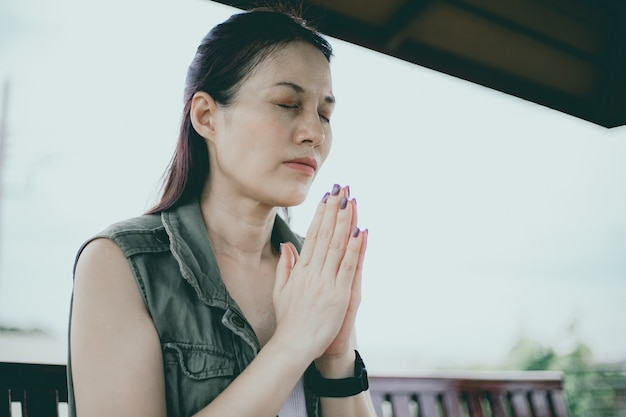 Femme asiatique priant le matin en plein air, mains jointes dans le concept de prière pour la foi, la spiritualité et la religion, concept en ligne des services de l'église.