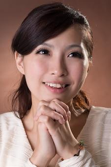 Femme asiatique priant, portrait agrandi sur fond marron studio.