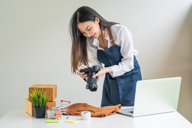 Femme asiatique propriétaire d'entreprise tenant un appareil photo pour prendre des photos de produits pour vendre en ligne un ordinateur portable et une boîte à colis à la maison.